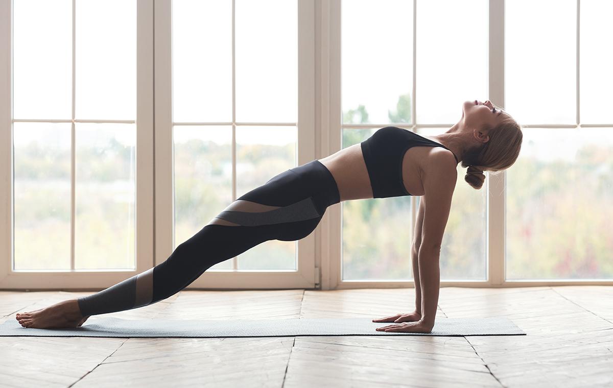 Flexible girl performing upward facing plank at yoga studio